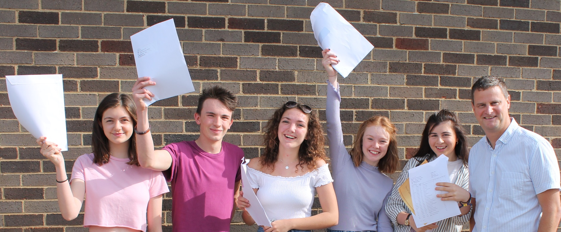 Imogen Tompkins, Ethan McHugo, Bethany Stirland, Lucy Wood and Lilian Veneziale celebrate their results with Mr. Taylor.